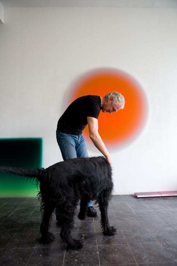 """Besuch bei Kuenstlern des Kreativ-Netzwerkes """"Made in Cologne"""". """"Made in Cologne"""" hat es geschafft, aus der virtuellen Welt zu realen monatlichen Treffen zu gelangen. Eine gute Gelegenheit, mal bei verschiedenen Kuenstlern von """"Made in Cologne"""" vorbeizuschauen. Auf diesem Bild sieht man den Maler Thomas Deyle zusammen mit Hund Goofy. Deyle hat einen sehr eigensinnigen Malstil. Eine spezielle Farbe wird auf dickes Acrylglas aufgetragen und erzeugt durch Lichteinwirkung eine gewisse Dreidimensionalitaet und ein Leuchten. Thomas Deyle hat sein Atelier bereits seit langem im grossten Kuenstlerhaus Deutschlands, dem Kunstwerk Koeln in der Deutz Mulheimer Strasse 127-129.  Aufnahmezeitpunkt:  07.05.2010,  12.47 Uhr"""