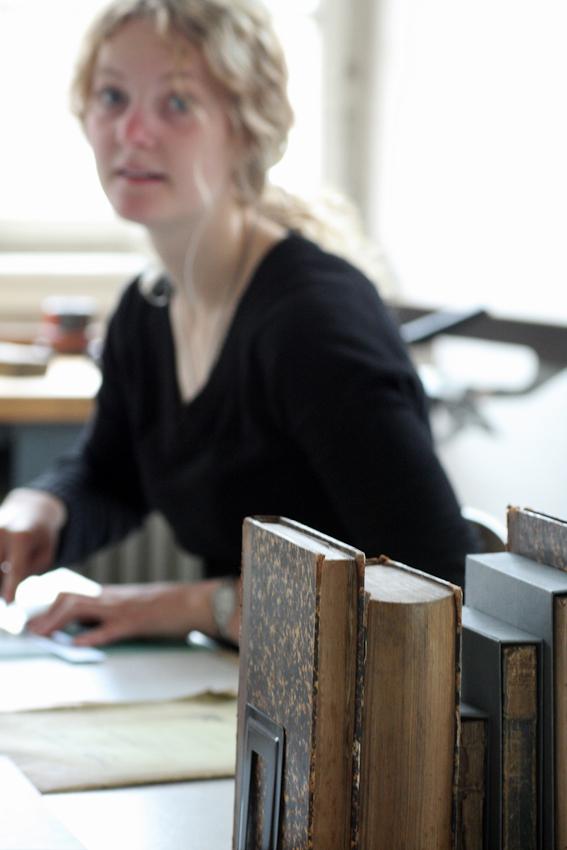 Vanessa Orlik ist studentische Hilfkraft der Buchbinderei der Universitätsbibliothek Mannheim. Die Werkstatt ist zuständig sowohl für das Buchbinden (meisten sind neue Bücher) als auch für Konservierung und Reparieren der alten Bücher, die vor 1850 erschien sind. Die Hiwi ist nur für Konservierung der alten Bucher zuständig. Gerade bastelt Vanessa Orlik eine Verpackung aus Pappe für ein altes Buch, weil viele Bücher einen extra Schutz brauchen. Das Fotos wurde um 10:42 an einem ihr ganz normalen Arbeitstagen aufgenommen.