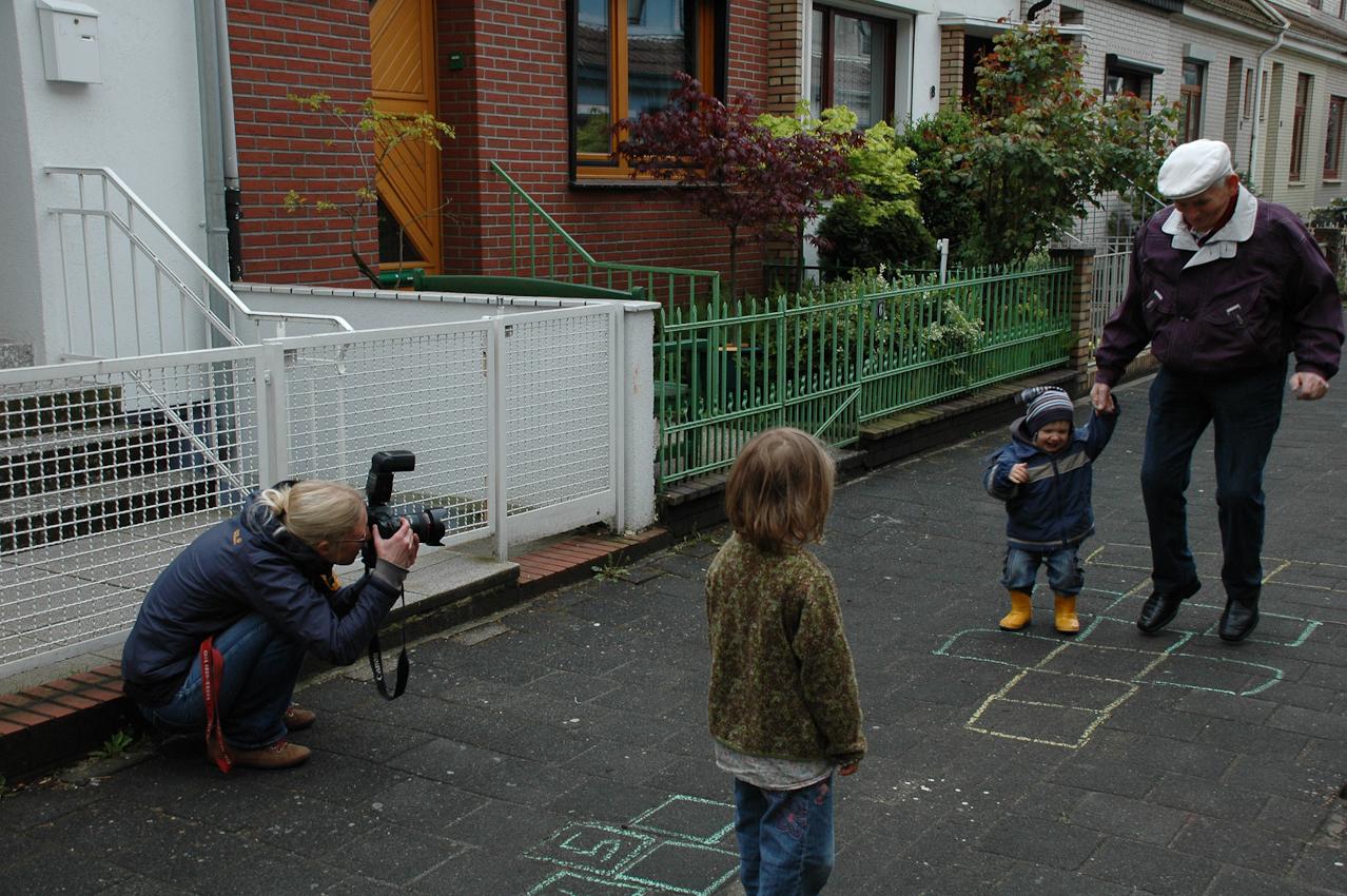 Fotografin Dunja Gediga fotografiert, in einer kleinen Straße in Bremen, Gert und Kolja,kleiner Junge,beim Hüpfkästchen-Springen. Mädchen Im Vordergrund schaut zu.