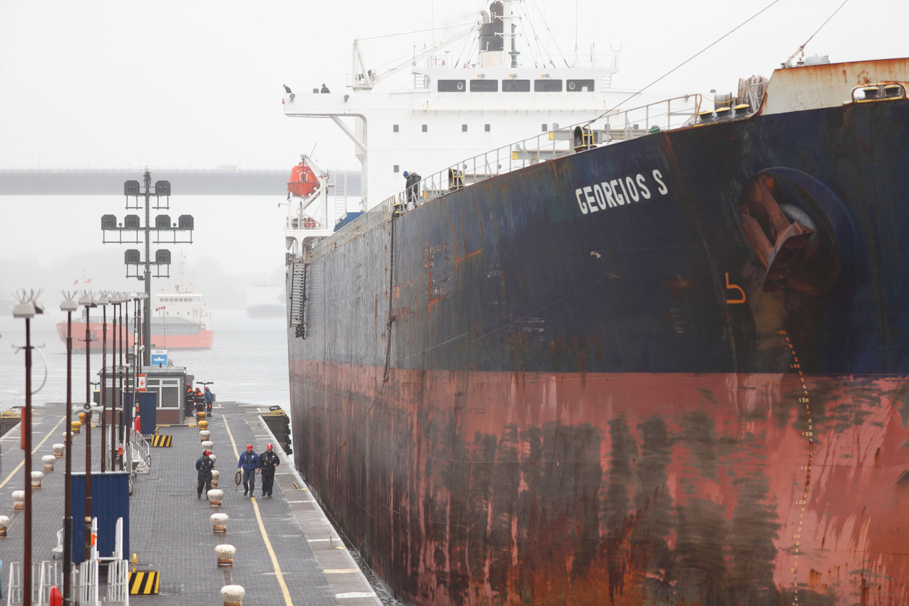 """Der Bulk-Carrier """"Georgios S"""" (IMO 9233507) beim Festmachen in der Holtenauer Schleuse. Von Westen aus - aus dem Nord-Ostsee-Kanal kommend - in die Nordkammer der Neuen Schleuse einlaufend, soll das Schiff festgemacht werden. Drei Festmacher gehen mit dem Schiff mit, um die Vorspring, die schon von der Schiffsbesatzung an der Wurfleine der Festmacher angeschlagen wurde, entgegen zu nehmen. Dies ist die erste Leine, die festgemacht wird, sobald das Schiff seine endgültige Position erreicht hat, mit dieser Leine wird das Schiff aufgestoppt. Drei weitere Festmacher warten am Ende des Mittelpfeilers auf die Achterleine. Die """"Georgios S"""" ist eines der größten Schiffe, die den Nord-Ostsee-Kanal passieren können (über 38000BRZ). Die Schleuse hat eine nutzbare Lange von 310m und eine nutzbare Breite von 40m. Das Schiff hat die Maße 225m x 32m, Heimathafen Piräus/Griechenland.  Im Hintergrund kommen weitere Schiffe unter den Hochbrücken aus der Regenwand und steuern die andere Schleusenkammer an."""