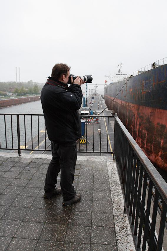 """Making of """"Ein Tag Deutschland"""". Thorsten Mischke fotografiert auf der Schleuse Kiel-Holtenau den Bulk-Carrier """"Georgios S"""" von der Terasse des Schleusenleitstandes aus."""