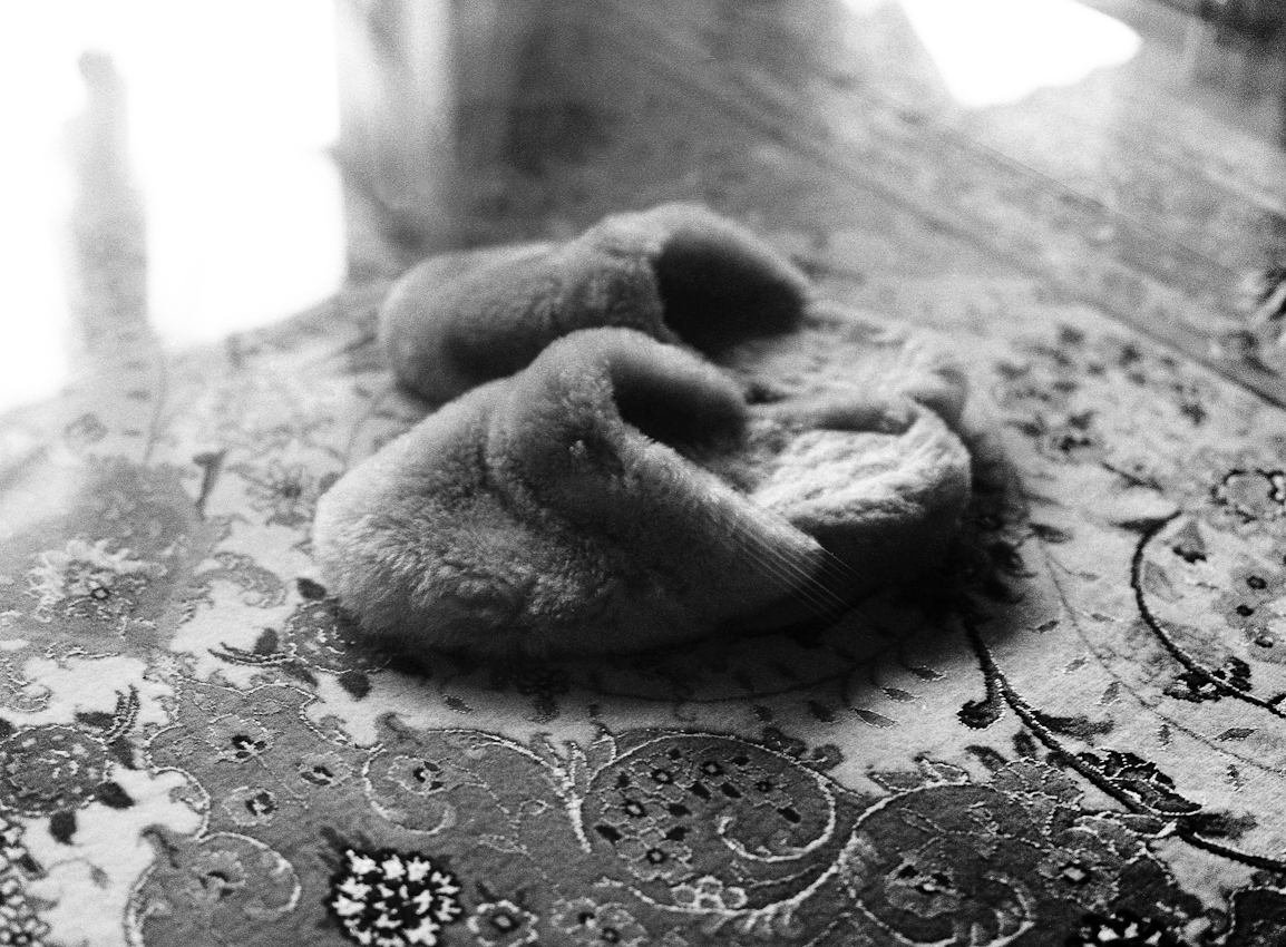 Pantoffeln auf dem Orientteppich im Wohnzimmer.