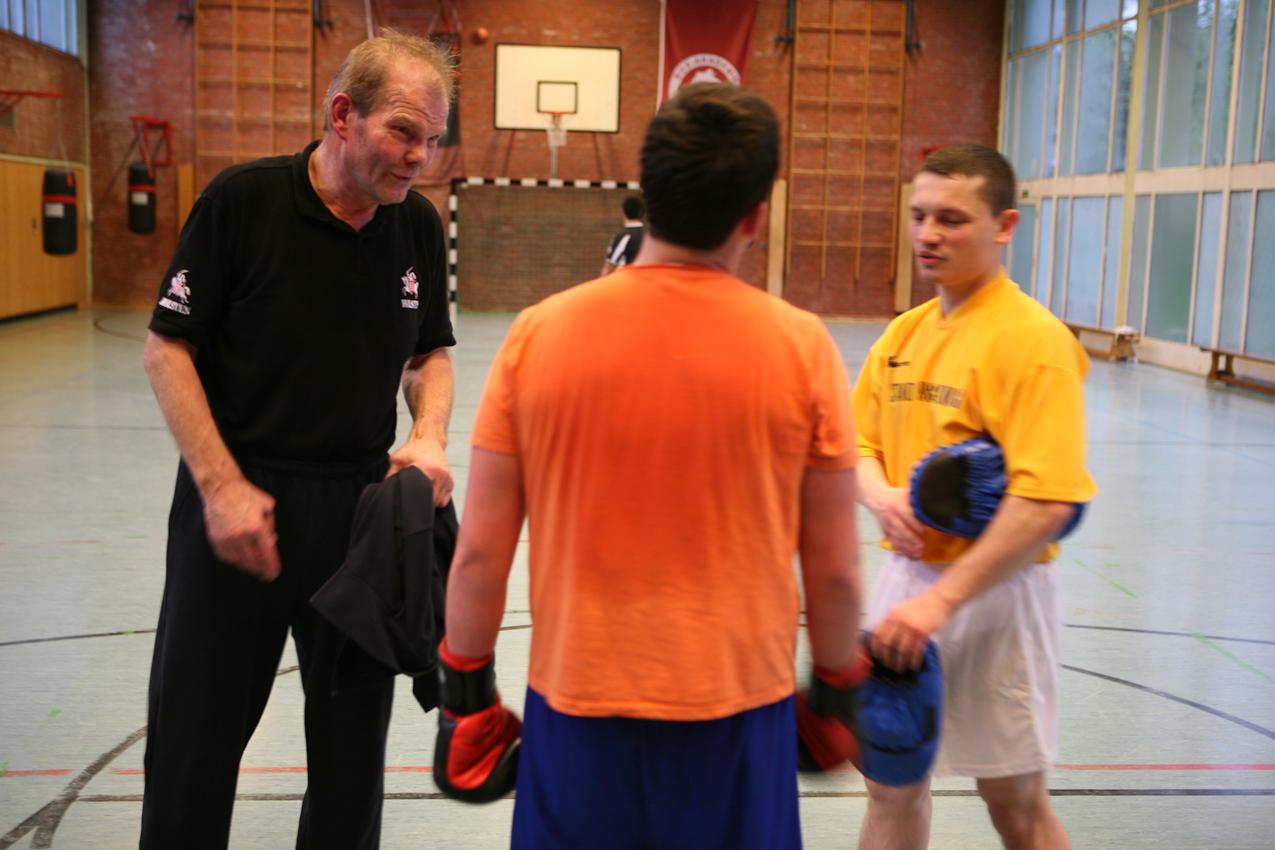 Jürgen Blin und Jugendtrainer Vitali geben Burak, 14, Tipps für's Pratzentraining.