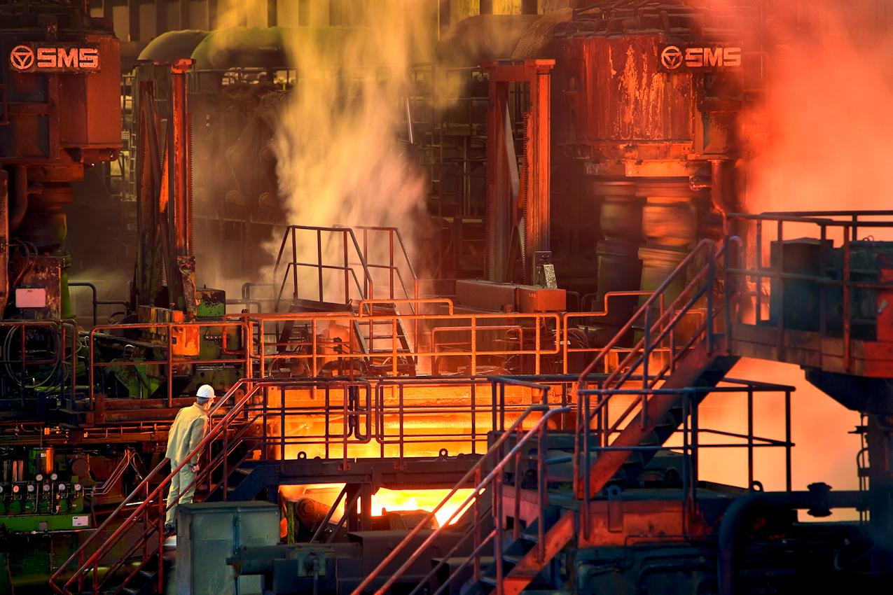 Warmwalzwerk Beeckerwerth. Brammen, produziert im Stahlwerk, werden im Warmwalzwerk zu Coils gewalzt. In der sonst menschenleeren Walzhalle kontrolliert ein Mitarbeiter den Lauf der tonnenschweren Stahlbrammen, die - rotglühend - mit atemberaubender Geschwindigkeit unter ihm vorbeirasen. In Duisburg befinden sich die modernsten und produktivsten Hochöfen, mittlerweile ist Shanghai an die erste Stelle der Stahlerzeugung aufgerückt.