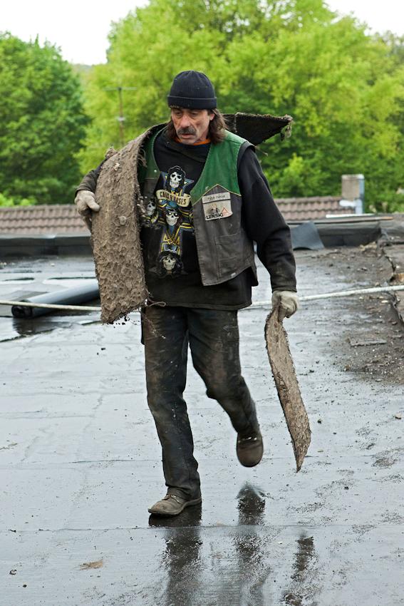 Ein Dachdeckerhelfer entfernt die alte Dachpappe.