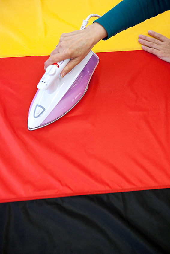 Eine Näherin bügelt eine große Deutschlandfahne.