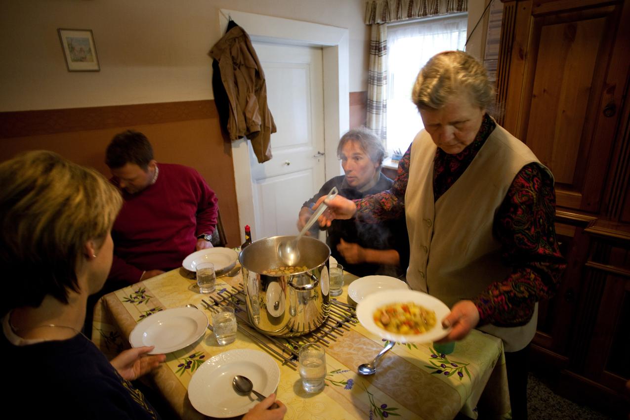 Siglinde Bruns (vorne rechts) und Christiane (links) haben gemeinsam  das Mittagessen gekocht. Um 12 Uhr kommen alle Familienmitglieder sowie Volker Fritsche (Aushilfe auf dem Hof, 43 Jahre alt) in der Hofküche zusammen, um gemeinsam Mittag zu essen. Heute gibt es passend zum nasskalten Wetter einen deftigen, selbstgemachten Gemüseeintopf mit Wursteinlage zum Aufwärmen.