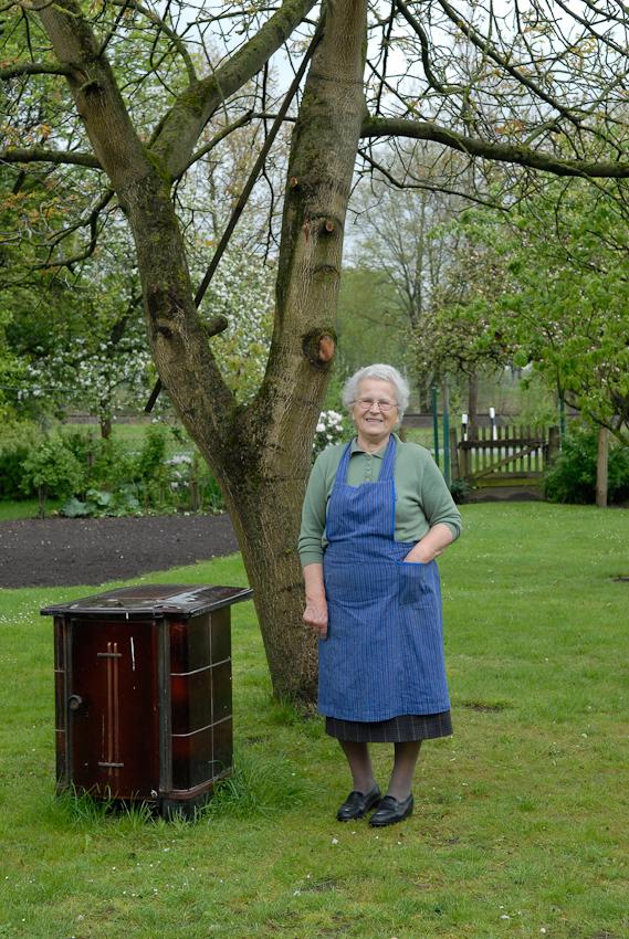 Emmi, Nachbarin aus meiner Kindheit in ihrem Garten in Tegelrieden, in ihrer typischen blauen Schürze neben einem Ofen aus den 50igern. Früher lebte sie hier mit ihren 3 Kindern, ihrem Mann und dessen Eltern, heute mit einer ihrer Töchter und 2 Enkelkindern.