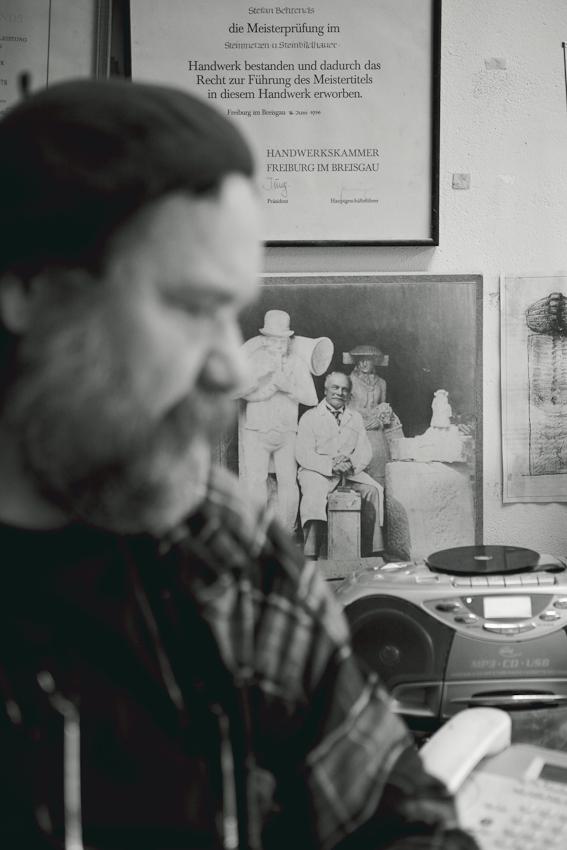 """Steinmetz und Steinbildhauer Stefan Behrends im Büro seiner Werkstatt in Hamburg-Volksdorf. An der Wand ein Foto des früheren Besitzers der Firma """"Schwabs Steinmetzbetrieb""""."""