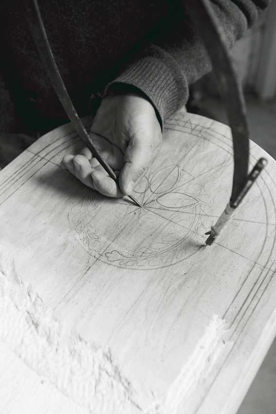Steinmetz Rüdiger Eckert beim Zirkeln eines Bogens für das Ornament, das auf den Sandstein eingemeißelt werden soll, in seiner Werkstatt in Hamburg-Wilhelmsburg. Er arbeitet an einem Grabmal, einer Auftragsarbeit.