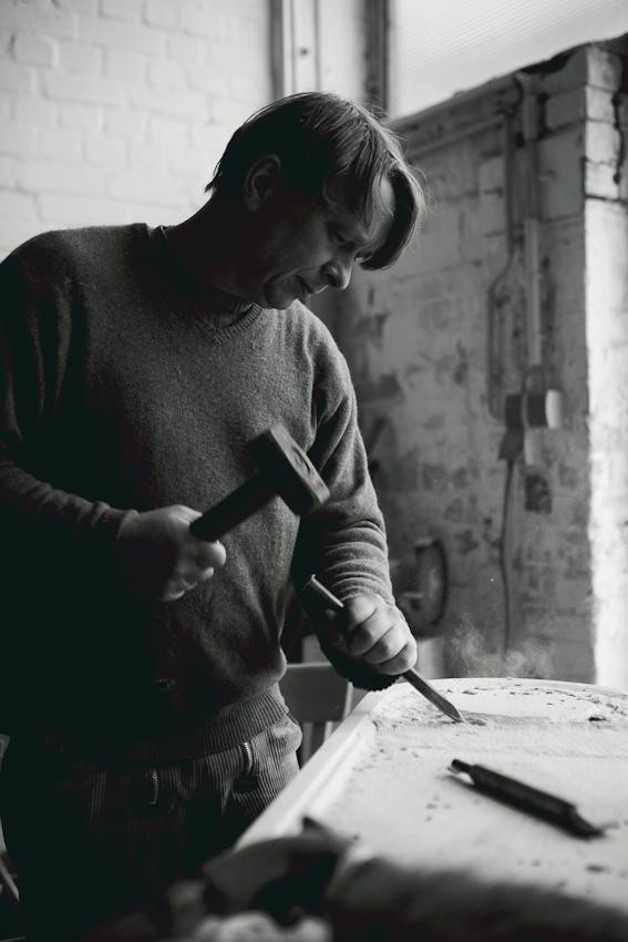 Rüdiger Eckert bearbeitet mit Hammer und Meißel einen Sandstein. Er arbeitet an einer Auftragsarbeit für ein Grabmal.