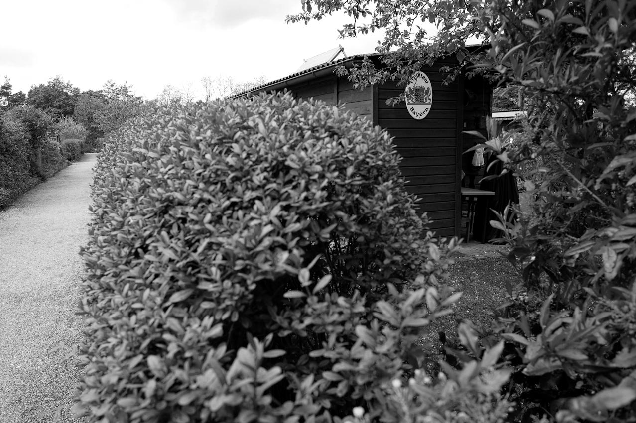 """Eine typisch hochgewachsene Hecke, um sich abzugrenzen und an dem Gartenhäuschen das Schild """"Freistaat Bayern""""."""