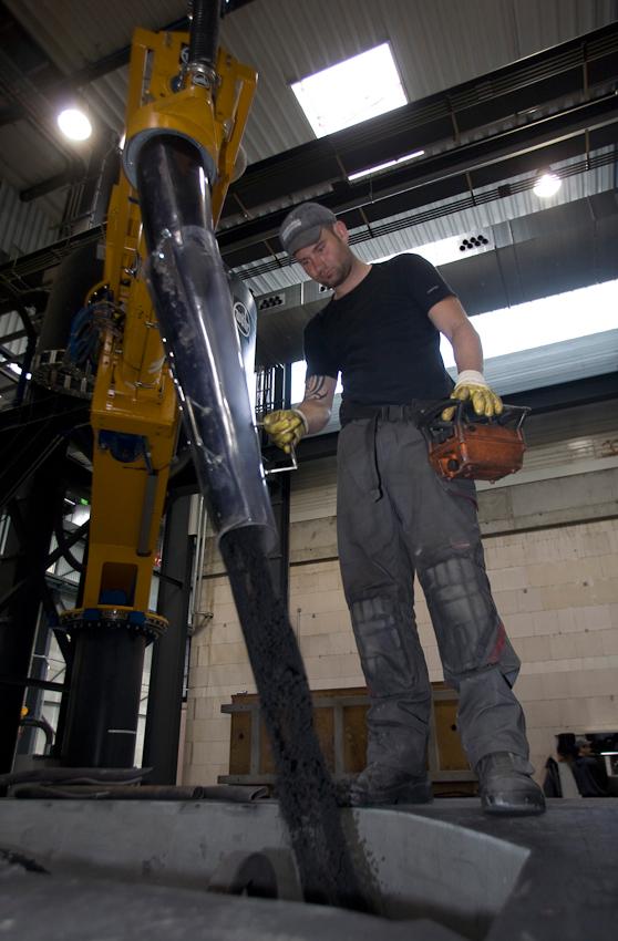 Gießerei HegerFerrit in Sembach bei Kaiserslautern. Hier werden Nabengehäuse für Windräder hergestellt. In der erst wenige Jahre alten Fabrik werden die Gießformen nach ihrer Fertigung auf Schienen von einer Station des Arbeitsablaufes zur nächsten befördert. Der Arbeiter lässt mit Harz gemischten Quarzsand in eine Gussform rieseln.