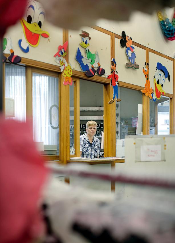 Heidi Habitz arbeitet als Pförtnerin in der Warenannahme des Kaufhauses C&A in der Kölner Innenstadt. Die Kunden kennen das Haus nur vom Haupteingang auf der Schildergasse. Hinter einem großen Rolltor an der stark befahrenen Nord-Süd-Fahrt ist Heidis Arbeitsplatz. Sie öffnet LKWs das Rolltor, nimmt eintreffende Ware entgegen und ist auch die Telefonzentrale des Hauses. Hier sitzt sie in der Pförnterloge, unscharf im Vordergrund stehen Wäschestander mit Damenünterwasche. Das Bild entstand am 7. Mai 2010 in der Warenannahme des Kaufhauses C&A in Köln.