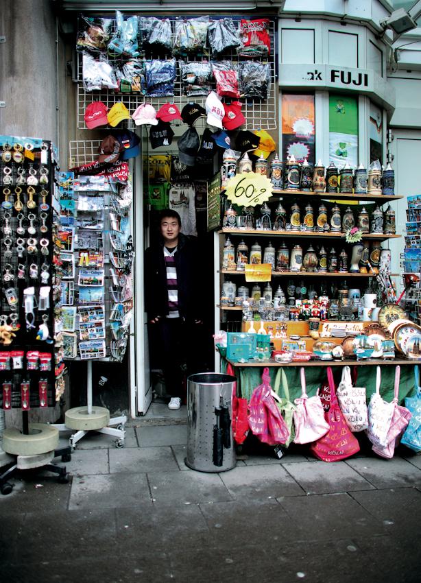 Yang Muyuan arbeitet im nach eigenen Angaben kleinsten Souvenirladen Kölns. Sein Geschäft liegt auf der Komödienstraße, keine 50 Meter von der Domplatte entfernt. Jeden Morgen räumt er seine Stände auf den Gehweg und sucht in seinem winzigen Laden Schutz vor Wind und Wetter. Das Bild entstand am 7. Mai 2010 an der Ecke Komödienstraße und Unter Fettenhennen in Köln.
