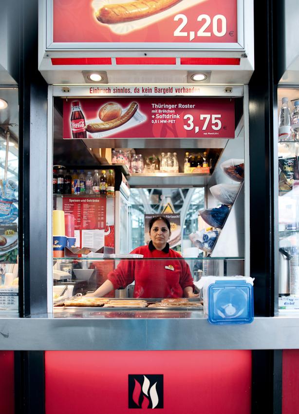 Komal Dhingra arbeitet in einem Wurststand auf Gleis 11 des Kölner Hauptbahnhofes. So auffällig der Stand auch ist, Komal selbst wird in der Alltagshektik auf dem Bahnhof von den tausenden Passanten oft kaum wahrgenommen. Der Kölner Hauptbahnhof ist mit rund 280 000 Reisenden pro Tag einer der am meisten frequentierten Bahnhöfe Deutschlands. Das Bild entstand am 7. Mai 2010 im Kölner Hauptbahnhof.