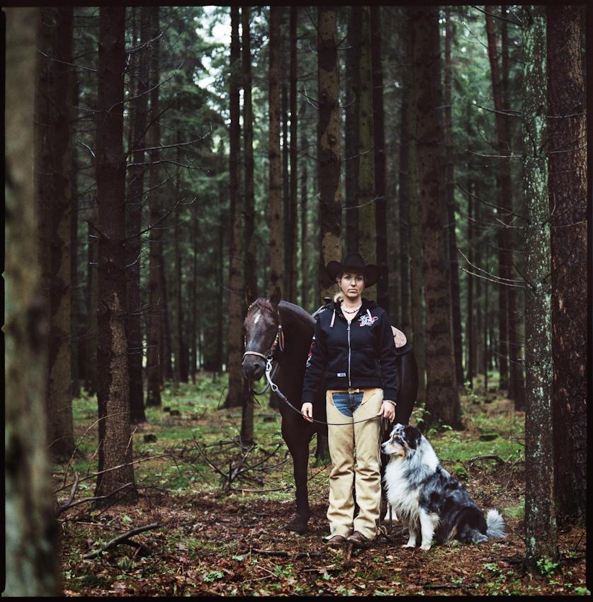 """""""Ein amerikanischer Traum"""", Familie Inndorf aus Jesteburg. 11.17 Uhr: Brigitte Inndorf steht mit ihrem Pferd Servus und ihrem Hund Mitch im Wald in der Nähe von ihrem Hof."""