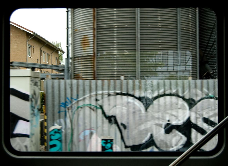 Blick aus dem Zugfenster um 13.56 Uhr. Ein Grafitti an einer Wellblechwand vor Wellblechsilos in Kamen.