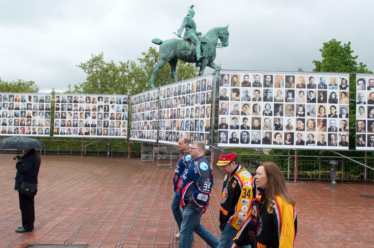 Gedenkinstallation mit Portraits von deportierten Zigeunern am Heinrich Böll Platz vor der Hohenzollernbrücke. Aufgenommen um 12:14 Uhr. Die Passanten im Vordergrund sind Eishockeyfans. Köln ist für sie vermutlich ein Zwischenstopp auf dem Weg nach Gelsenkirchen, wo die Eishockey-WM an diesem Tag mit dem Spiel Deutschland gegen die USA eröffnet wird.
