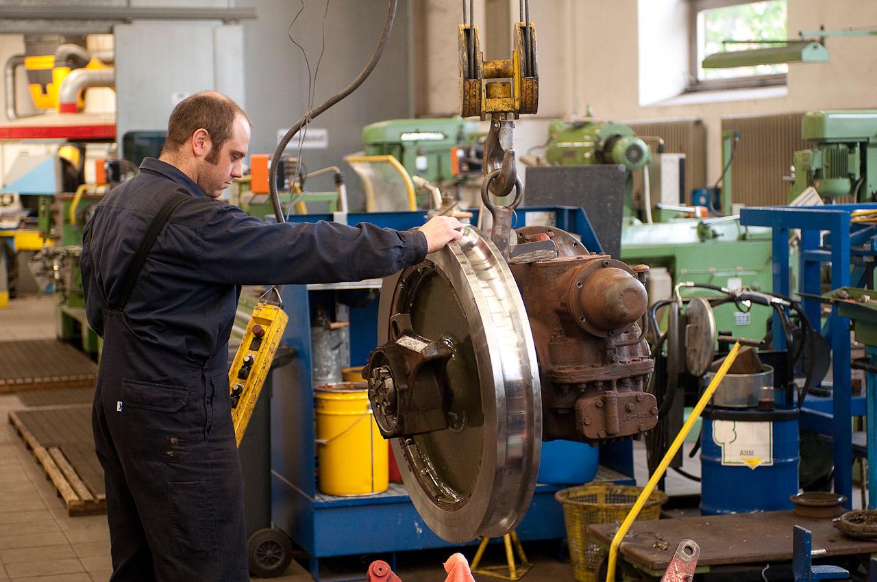 Christian Haan bei der Radmontage am Getriebe eines Schwebebahn- Gelenktriebwagens in der Fahrzeugwerkstatt in Wuppertal Vohwinkel.