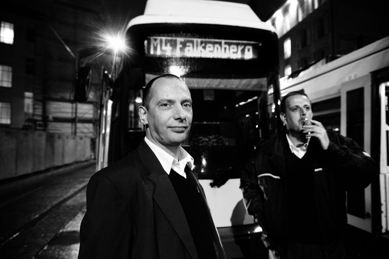 Die Tram-Fahrer der BVG (Berliner Verkehrsbetriebe) Andreas Strelow (45) und Uwe Sichert (46) stehen morgens gegen 04.30 Uhr am Hackeschen Markt in Berlin vor 'ihren' Tramlinien. Bei leichtem Nieselregen wird noch schnell eine Feierabendzigarette geraucht, bevor es nach Hause geht.