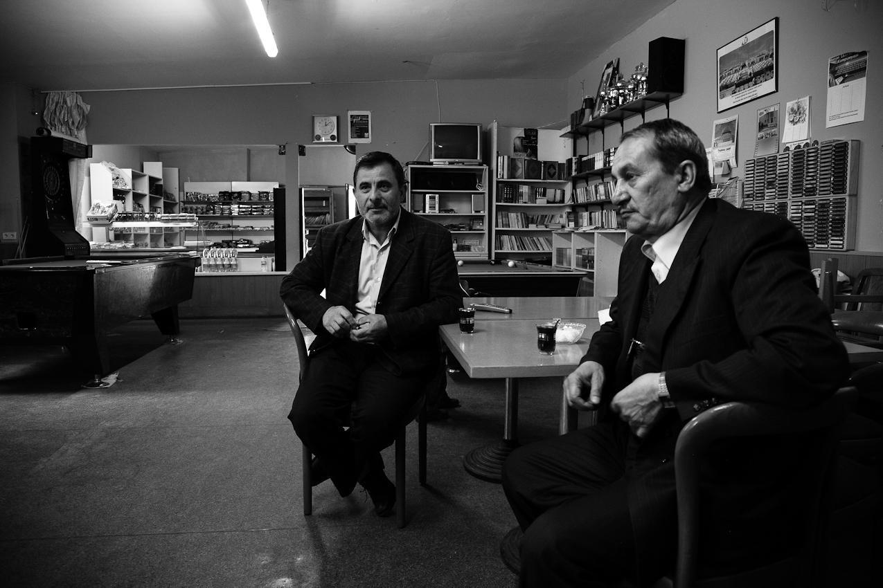 Im Gemeinderaum der Takva-Moschee Leipzig erwartet der Imam (rechts) mit einem Mitglied der Gemeinde das Eintreffen der Gläubigen. Die beiden trinken Tee, im Hintergrund sieht man einen Billiardtisch, an welchem man erkennt, dass die Räumlichkeiten auch eine weltliche Nutzung erfahren.