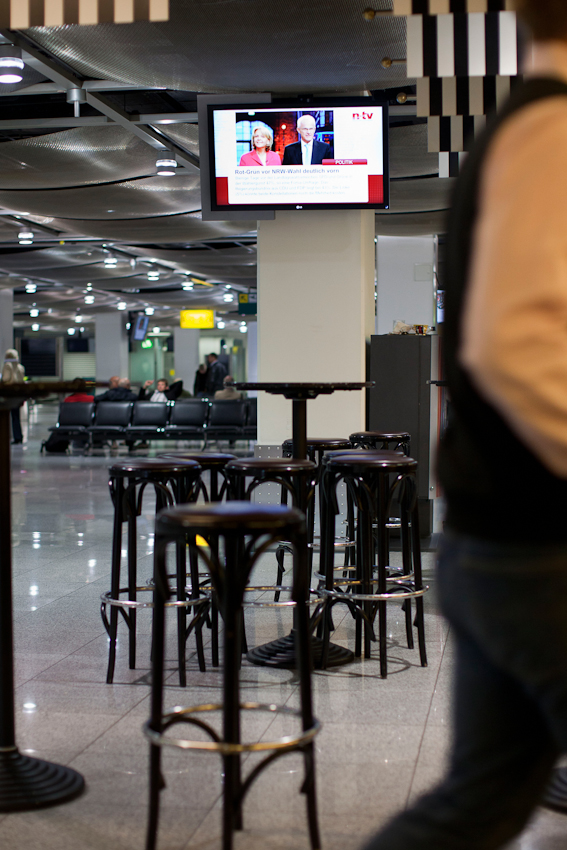 Morgen des 7. Mai am Flughafen Duesseldorf. Der Fernsehsender n-tv meldet, dass rot-gruen, kurz vor der Landtagswahl in Nordrhein-Westfalen, in den Umfragen vor schwarz-gelb liegt. Am Gate scheint sich niemand dafuer zu interessieren.
