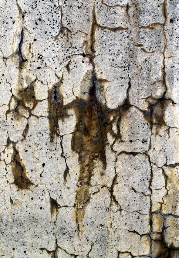 15:09 Uhr - Muster in einer Betonmauer am Karlsruher Rheinhafen. Bestandteile der rostenden Metallträger in der Mauer treten durch Risse und Löcher an die Oberfläche.