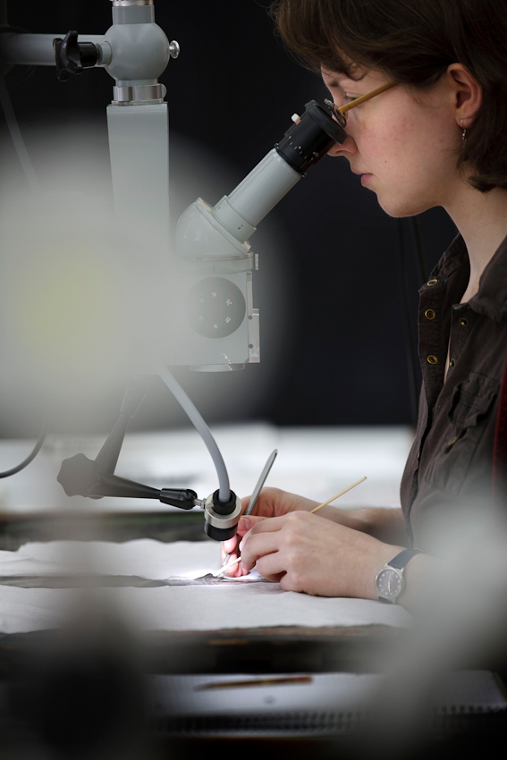 Eine Restauratorin kratzt ganz vorsichtig alte Übermalungen unter dem Mikroskop ab.