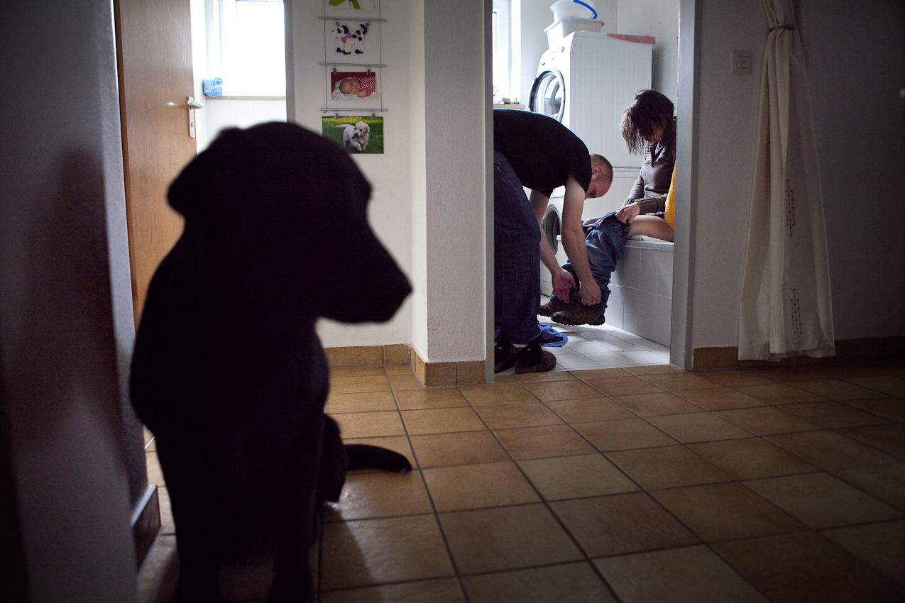 """Corinna (28 Jahre alt) hat von Geburt an eine körperliche Behinderung. Seit ein paar Monaten hilft ihr im Alltag ihr Behindertenbegleithund Luna. Luna wurde von dem österreichischen Verein """"Partner-Hunde"""" ausgebildet und mit Hilfe des niedersächsischen Vereins """"Apporte"""" aus Wunstorf finanziert. Corinna lebt zusammen mit ihrem Lebensgefährten Fabian in Fürstenfeldbruck, in der Nähe von München. Menschen mit körperlicher Behinderung sind häufig in ihrer Eigenständigkeit eingeschränkt. Sogenannte Assistenz- bzw. Servicebegleithunde wie z.B. Blindenführhunde, Signalhunde oder eben Behindertenbegleithunde wie Luna ermöglichen ihren Besitzern mit Behinderung ein eigenständigeres Leben und haben auf die Psyche des Menschen eine überaus positive Wirkung. Blindenbegleithunde werden in Deutschland bereits vollkommen durch die Krankenkassen finanziert und bekommen Zutritt in allen Geschäften - die nicht minder bedeutungsvollen Behindertenbegleithunde sind leider noch weniger anerkannt und werden nicht von den Krankenkassen finanziert, sondern über gemeinnützige Vereine und Spendenaktionen. Nach der Morgentoilette wird Corinna von ihrem Lebensgefährten Fabian in der gemeinsamen Wohnung in Fürstenfeldbruck (in der Nähe von München) angezogen. Die Hündin Luna wartet bereits in nicht allzu großer Entfernung auf Kommandos, ihrer Besitzerin Hilfestellung zu leisten."""