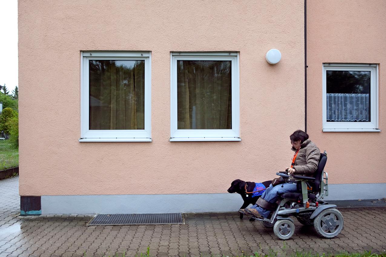 Corinna und Luna auf dem morgendlichen Weg zur Arbeit. Im Hintergrund ist die Wohnung von Corinna und Fabian zu sehen, welche sich im Erdgeschoss eines Wohnblocks, nicht weit von Corinnas Arbeitsstelle befindet.