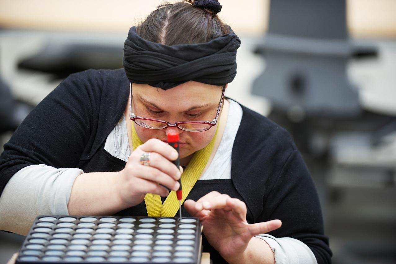 Im Bereich Industriemontage platziert eine Mitarbeiterin mithilfe eines Schraubenziehers präzise kleine Gummiringe in Kuststoffformen.