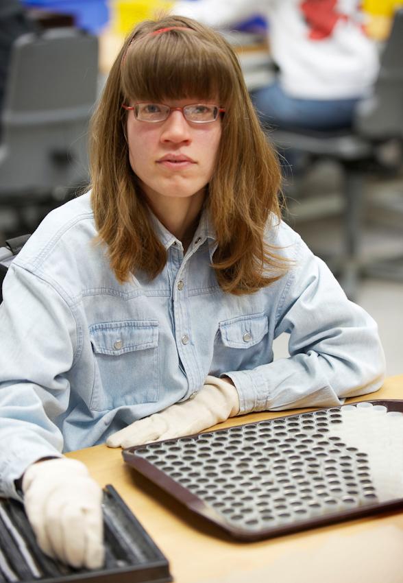 Eine Mitarbeiterin der Abteilung Industriemontage fügt Stahlringe in Plastikschalen zur Weiterverarbeitung in der Automobilindustrie.