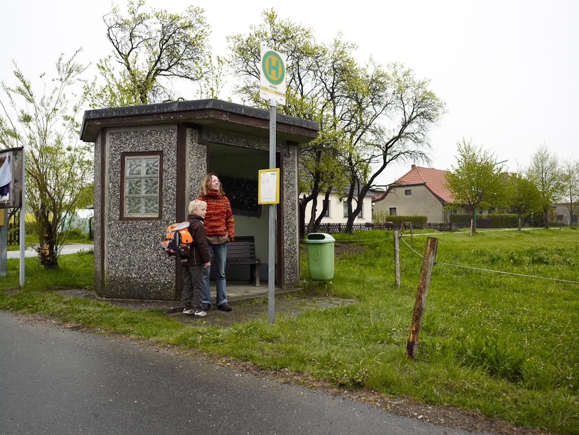 Eine Mutter wartet mit ihrem Sohn auf den Schulbus.