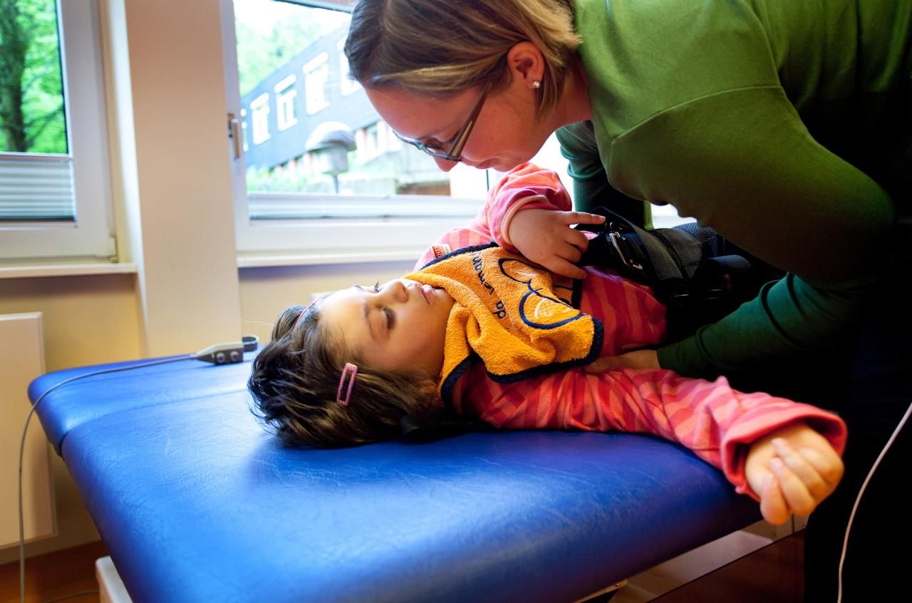 Milena in der Bewegungstherapie. Hier mit Milenas Therapeutin, die sie für Übungen auf dem Gangroboter vorbereitet.
