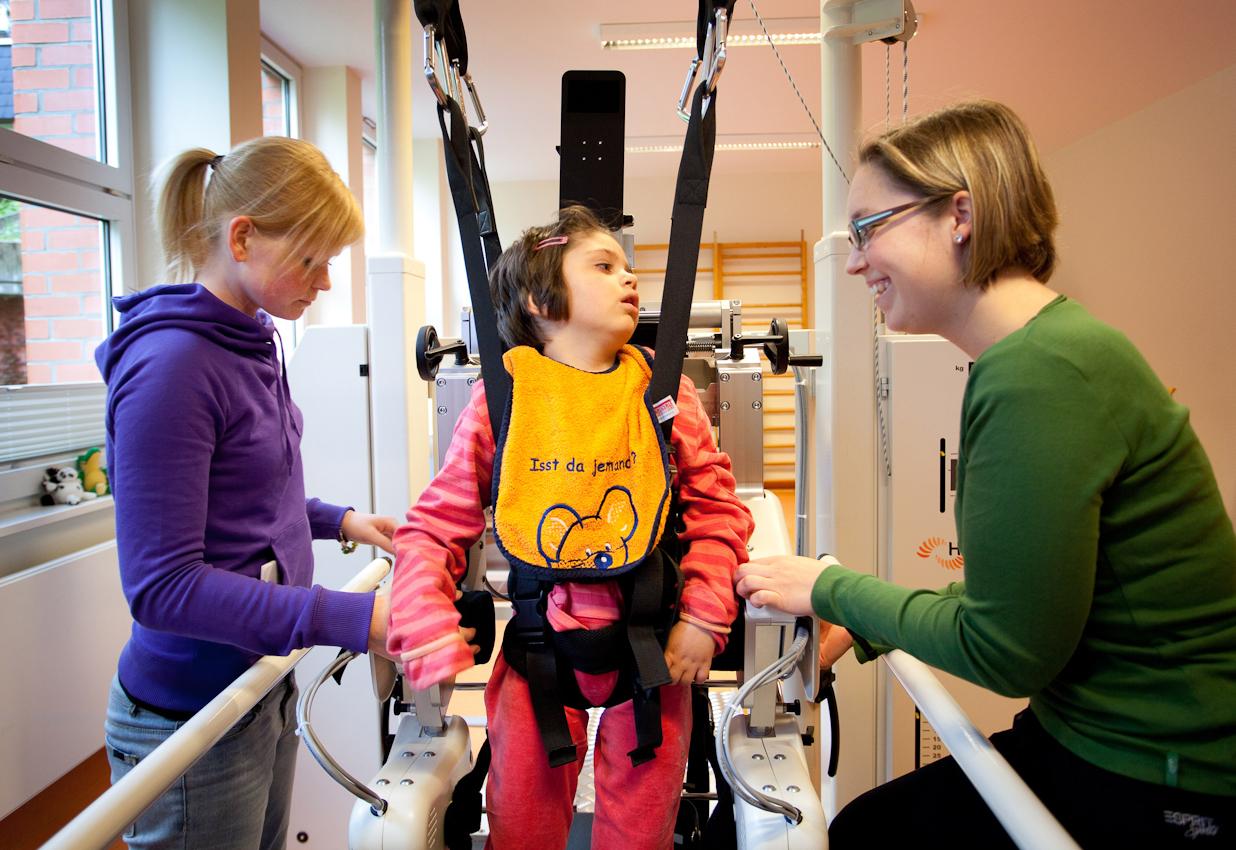 Milena in der Bewegungstherapie. Am Gangroboter lernt sie wieder zu laufen.