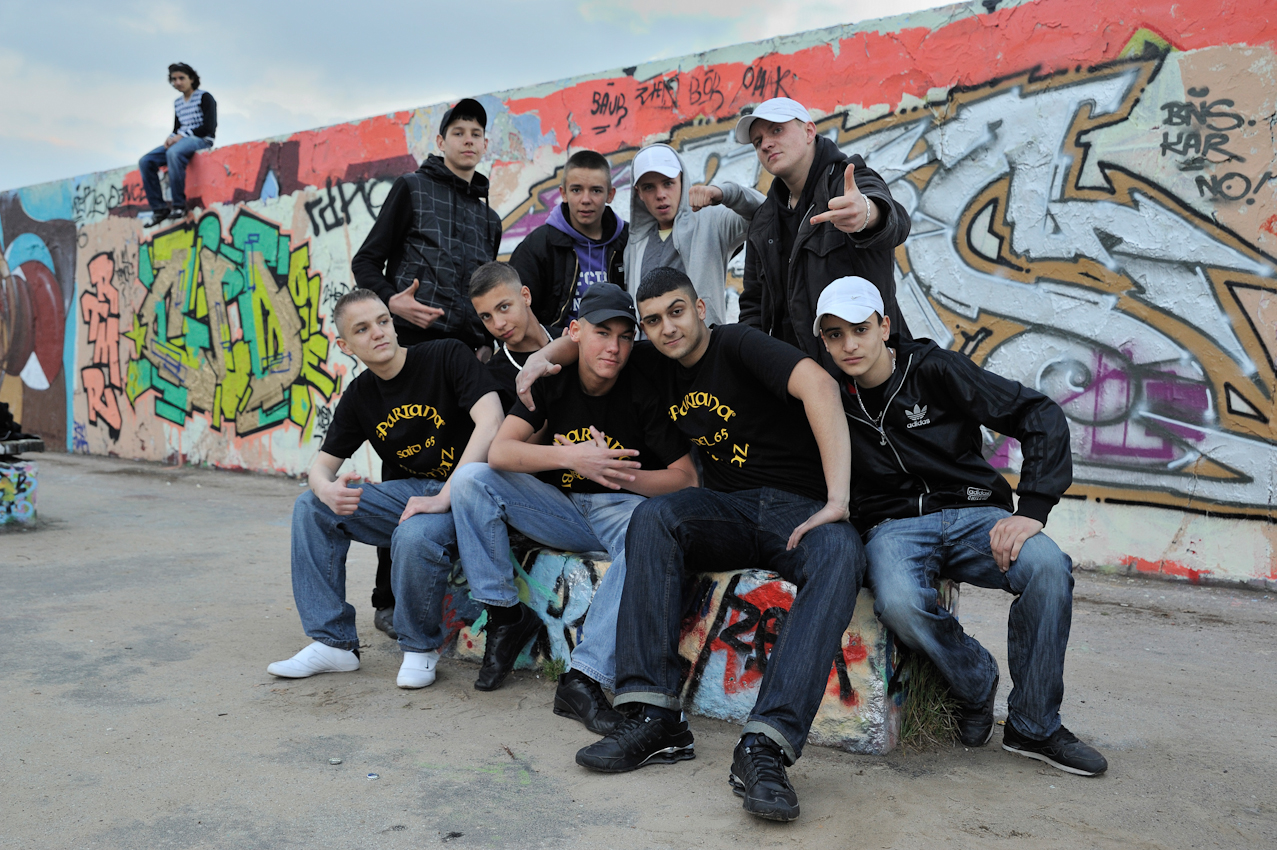 """Gruppe junger Migranten, im Vordergrund die Rapper - Gruppe """"Spartana Brothaz"""", vor mit Graffiti besprühter inneren Mauer."""