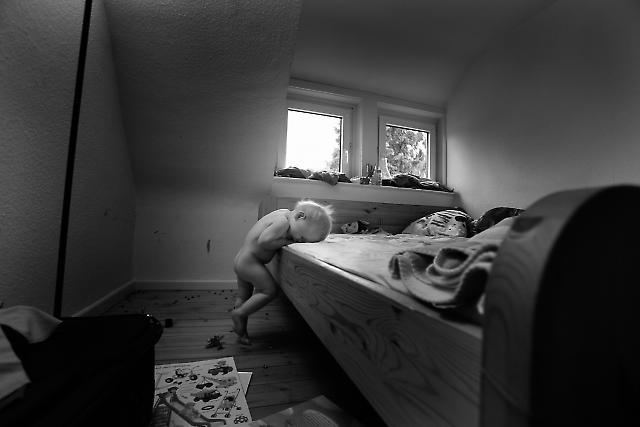 Elias ist frustriert, weil er es nicht schafft, alleine auf das Bett seiner Eltern zu klettern. ----- Titel:  Ganz bei sich -- Ein Tag im Leben von Elias Valentin Morascher; Sohn des Fotografen Arnold Morascher. Mein Hauptinteresse bestand darin, das Kind nicht in Interaktion mit anderen sondern in Konzentration auf sich selbst zu fotografieren. Die Serie zeigt die Eigenständigkeit des 18 Monate alten Kindes (geboren 14.11.2008),  die konzentrierten Momente. Lernen, Erfahren, Bewegung, selbständiges Spielen; auch die Frustration des Kindes, als es z.B. nicht in der Lage ist, alleine auf das Bett der Eltern zu klettern. Die Serie entstand in etwa vier Stunden zwischen 13:00 und 17:00 Uhr am 07.05.2010 und zeigt ein Stück Leben eines Kleinkindes in Deutschland /22175 Hamburg/Bramfeld.
