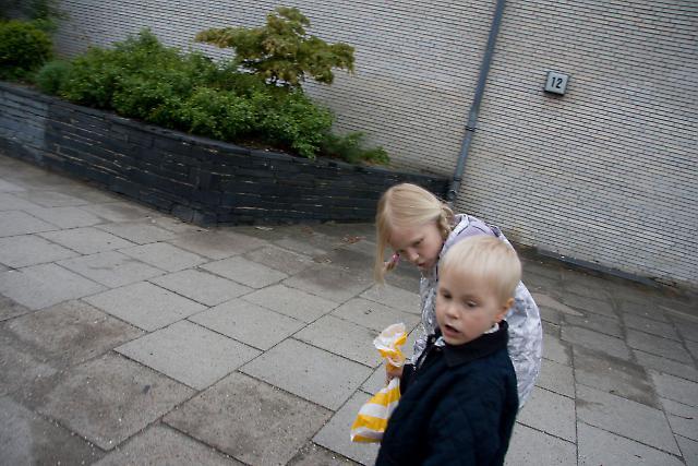 Ein blondes Geschwisterpärchen am Straßenrand in Hamburg-Eimsbüttel (Gartnerstraße 12, 20253 Hamburg). Der kleine Bruder hält eine Brötchentüte in der Hand.