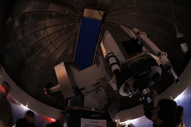 Im Kuppelraum der Bayerischen Volkssternwarte Neumakt/Opf. stellt Harald Liederer das Spiegelteleskop für eine Besuchergruppe zur Beobachtung ein.